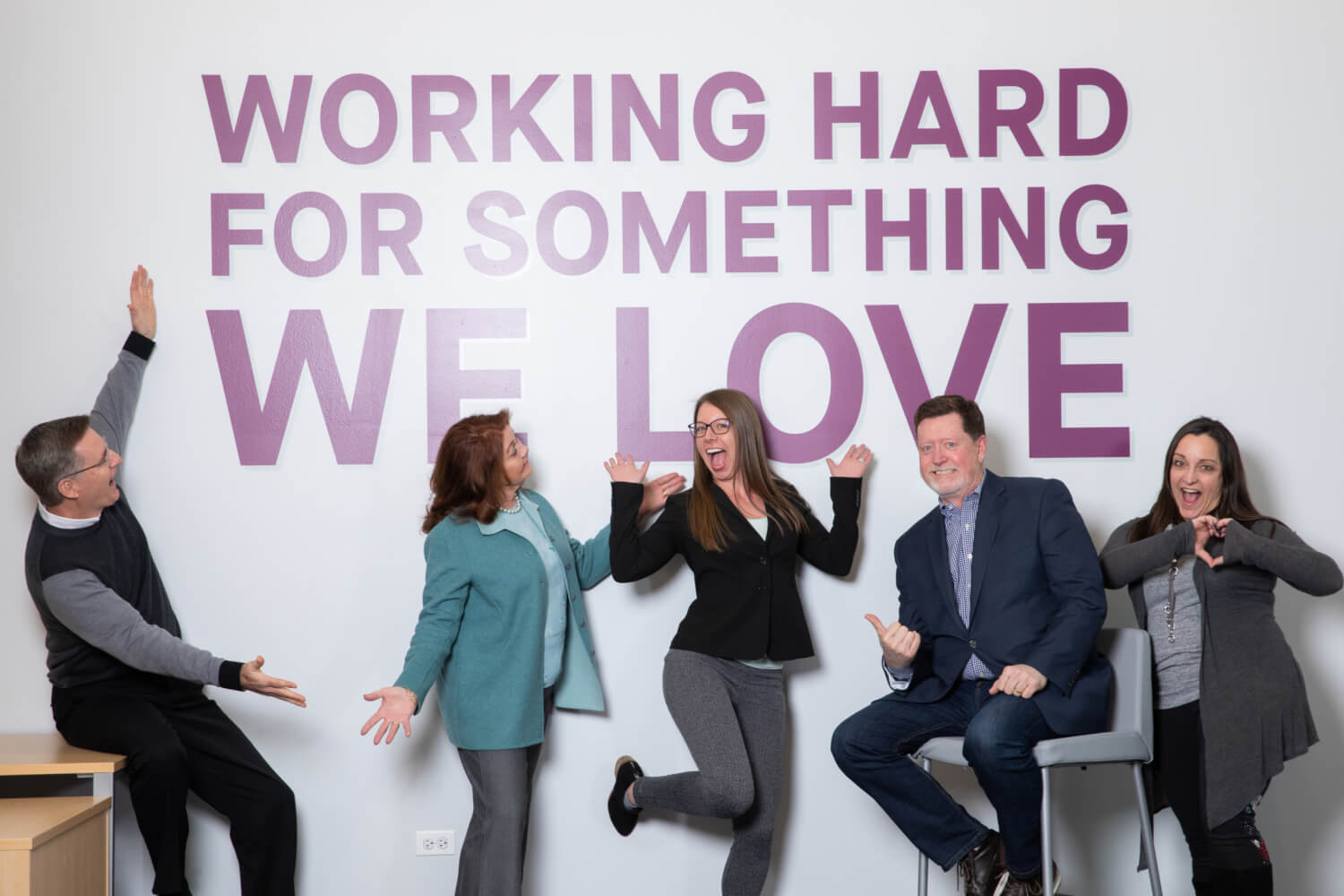 """five members of the solopreneur group in front of a wall saying """"Working hard for something we love"""""""